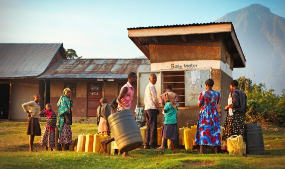 Nyarusiza, Uganda - May 28, 2017: Local villagers waiting with plastic canisters to get safe water from public water well